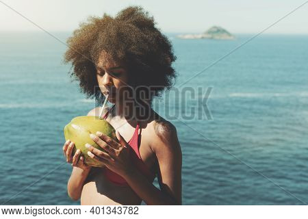 A Tranquil Cute Young African-american Female With Curly Afro Hair Is Drinking Coconut Water From Re