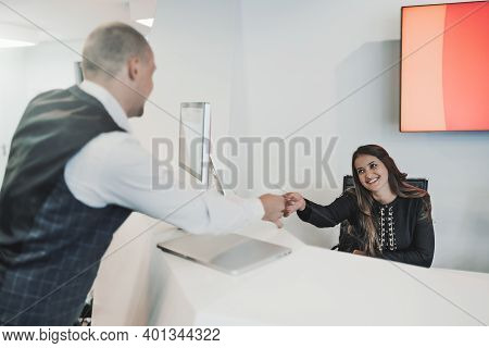 A Cheerful Female Receptionist Is Giving A Man Entrepreneur With A Laptop A Pass Card To Office Faci