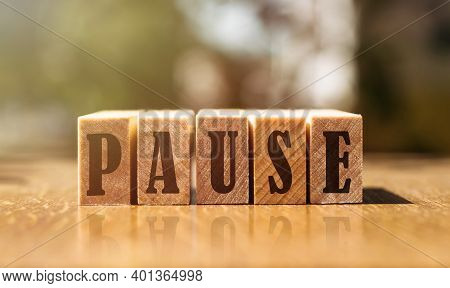 The Word Pause From Wooden Blocks On The Table In The Sunlight.