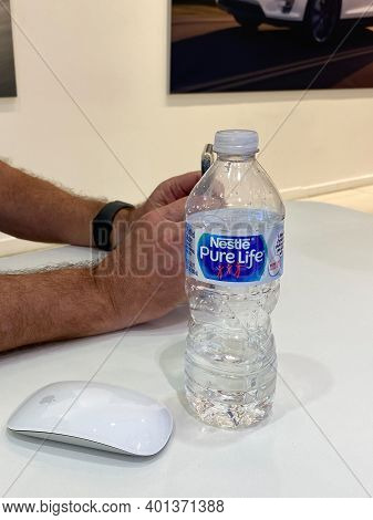 A Bottle Of Nestle Water Sitting On A White Table Next To An Apple Mouse.