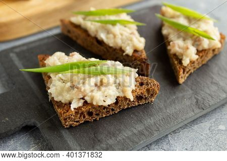 Three Toasts Or Canapes With Herring Forshmak On A Tapas Board. Forshmak On Rye Bread Canape With Gr