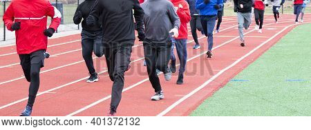 A High School Boys Winter Track Team Running On A Track Covered Up With Spandex And Sweatpants On Th