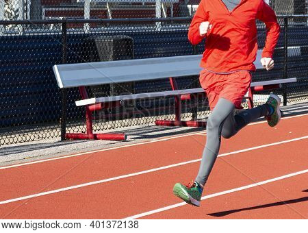 A High School Boy Is Running Fast On A Red Track In The Sunshine On A Cold Day.
