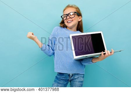Joyful European Girl Holding A Computer In Her Hands With Mockup On A Light Blue Background.