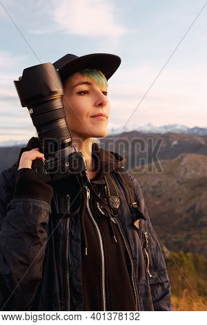 Young Photographer With A Serene And Accommodating Gesture, Receiving The Evening Sun On His Face Wi