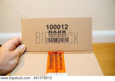 Paris, France - Dec 8 2020: Pov Male Hand Holding Cardboard Parcel Box With Logotype Of Bahr Packagi