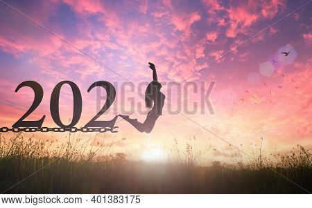 Success New Year 2021 Concept: Silhouette Of A Woman Jumping And Broken Chains With Text For 2021 At