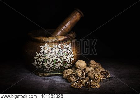 Handmade Wooden Mortar With Alpine Decorations And Nuts To Beat. High Quality Photo