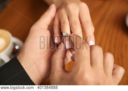 Man Putting Engagement Ring On His Girlfriend's Finger In Cafe, Closeup