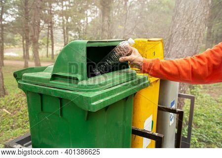 Hand Of Woman Throwing Plastic Bottle Into Old Trash Can, Concept Of Environmental Protection, Litte