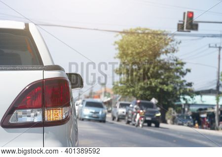 Luxury Rear Corner Of Pickup White Car On The Road. Stop By Red Traffic Signal At The Intersection.