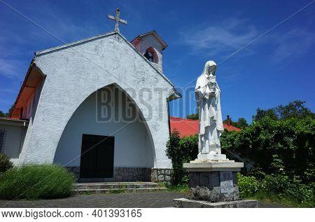 Pucon, Chile - December 6, 2018: White statue next to Santa Clara de Pucon Monastery white church, Blue sky, sunny day