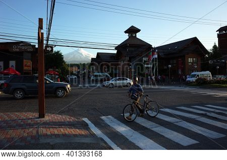 Pucon, Chile - December 8, 2018: Main street in town, Man with bicycle crosses road at pedestrian crossing, View of snow capped Villarrica volcano, A lot of electric wires, Evening light