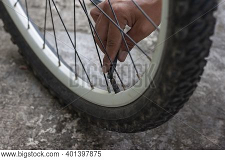 Hand Of Mechanic Holding A Hard Plastic Rod Pressed The Air Valve To Deflate The Bicycle Wheel.