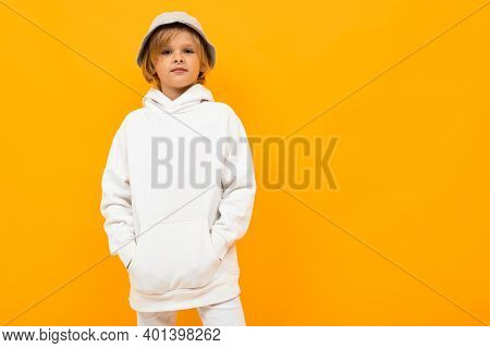 European Boy With A Panama In A White Hoodie On A Yellow Background.