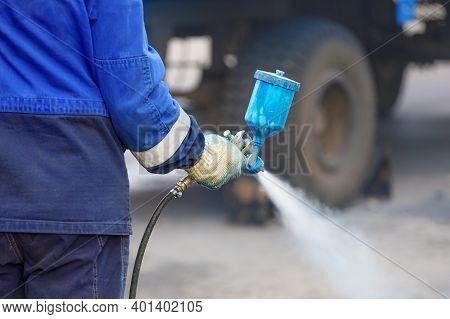 Spray Gun In Hand. A Worker In Overalls And A Glove Holds A Spray Compressor For Painting In His Han