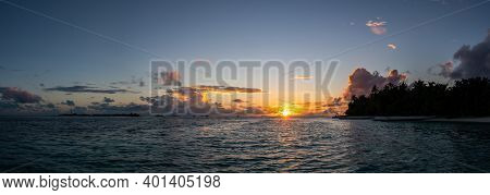Dramatic Maldivian Sunset Over The Ocean With Cumulonimbus Clouds On The Horizon And Silhouettes Of