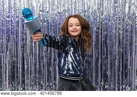 Funny Beautiful Holiday Host Holds The Microphone Up On A Background Of Shiny Tinsel.