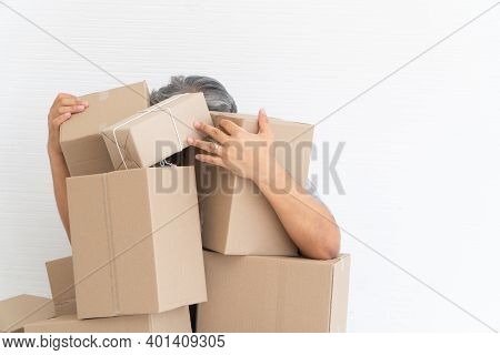 Asian Shopaholic Sitting On The Floor In The Living Room And Cardboard Box On Top Of Him After The C
