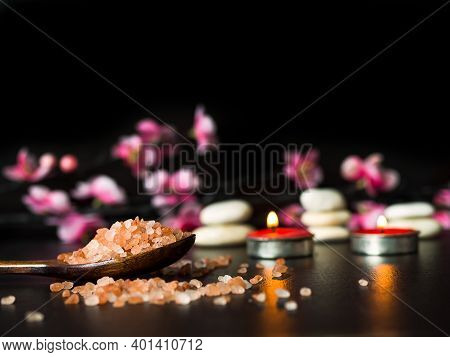 Himalayan Salt Spa Aromatherapy With Candle And Pebbles, Pink Flowers On Black Dark Tone Background.