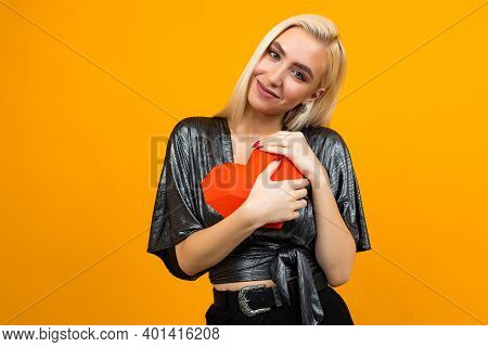 Attractive Caucasian Girl Hugs 3d Heart Figure On Orange Studio Background. Valentines Day.