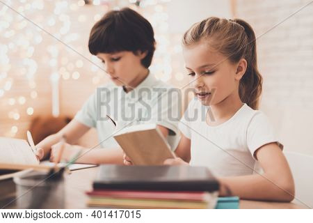 Children At Home. Brother Is Writing And Sister Is Reading, They Are Doing Homework.