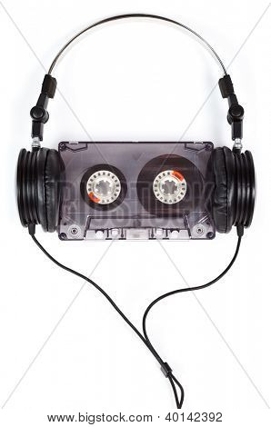 Compact headphones with audio cassette on white background