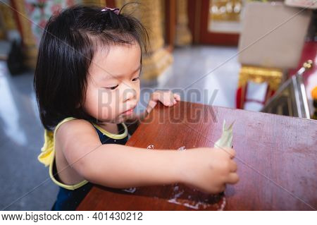 Asian Baby Child Girl Is Using A Hand To Hold A Banknote To Put In A Box To Donate Or Make Merit In