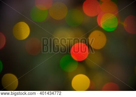 Blurred Background Of Bright Christmas Garland Lights On Christmas Tree Full Of Mist.