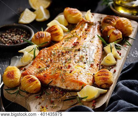 Roast Salmon Fillet Seasoned With Herbs And Lemon With Hasselback Potatoes, Close-up View