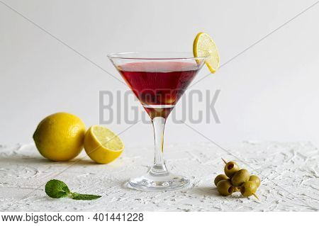 Cosmopolitan Cocktail In The Bar. Martini Glass Of Red Cocktail With Olives And Lemon On White Backg