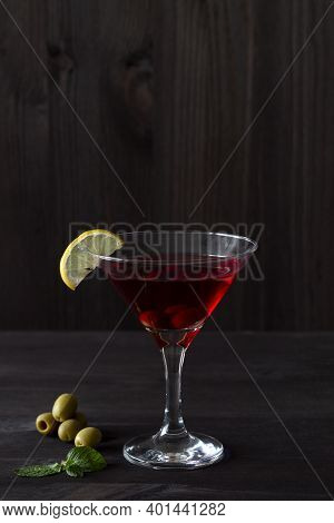 Cosmopolitan Cocktail In The Bar. Martini Glass Of Red Cocktail With Olives And Lemon With Green Min
