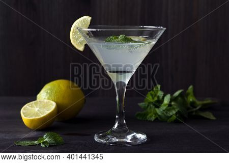Margarita Cocktail In The Bar. Martini Glass Of Cocktail With Olives And Lemon With Green Mint On Wo
