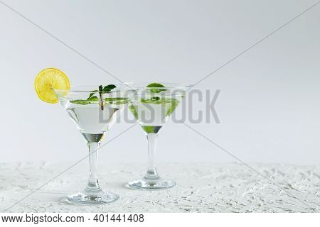 Cocktail In The Bar. Two Martini Glasses Of Cocktail With Green Mint And Lime On White Background. A