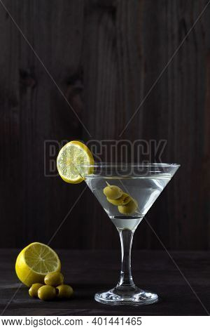 Margarita Cocktail In The Bar. Martini Glass Of Cocktail With Olives And Lemon On Wooden Background.