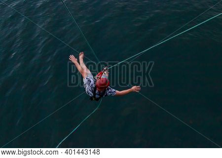 Rope Jumping From High Altitude Of Bridge. Bungee Jumping From Pedestrian Bridge Over Beautiful Rive
