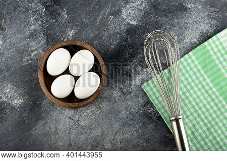 Bowl Of Raw Eggs And Whisker On Marble Background