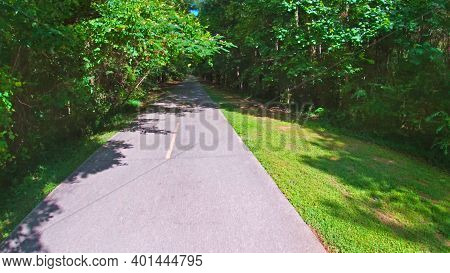 Paulding County, Ga Usa - 06 11 20: Paved Trail Side Ahead View With Green Foliage In The Summer Sil