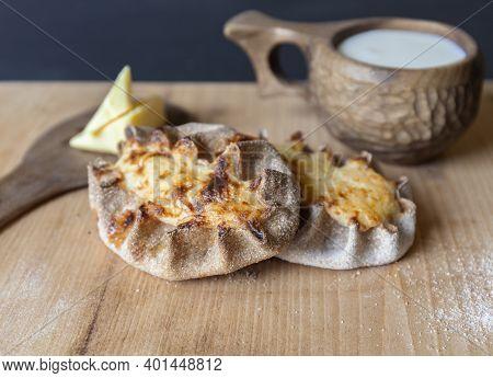 Finnish Traditional Pasties - Karelian Pies From Region Of Karelia. Table With A Wooden Mug Kuksa Fu