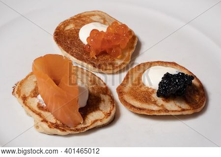 Mixed Blinis With Smoked Salmon, Rad And White Caviar Garnished With Sour Cream On A White Plate