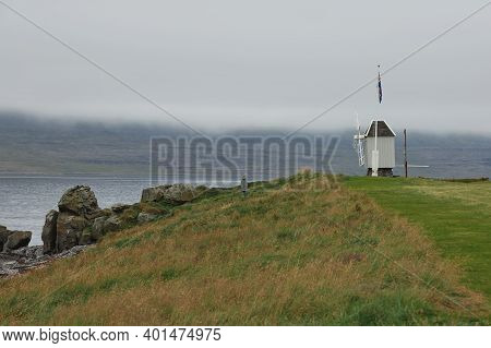 Windmill And Icelandic Flag In Vigur Island In A Cloudy And Windy Day, Iceland