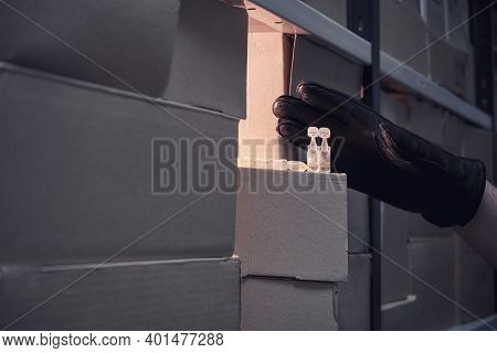 A Man Hand In A Black Glove Picks Up The Last Medicines From The Warehouse. Virus Vaccination Proble