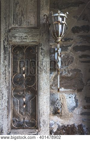 View Of An Old Fashioned White Metal Lantern On The Wall And A Worn Door