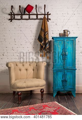 Classic Beige Armchair With Wooden Legs, Vintage Turquoise Cupboard, Wall Hanger, And Ornate Scarf O