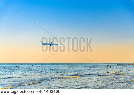 Airplane Flying Low Above Sea And People Tourists Swimming In Water, Clear Blue Orange Sky At Sunset