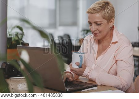 Lovely Mature Female Entrepreneur Working At Her Office, Using Laptop. Charming Beautiful Mature Bus