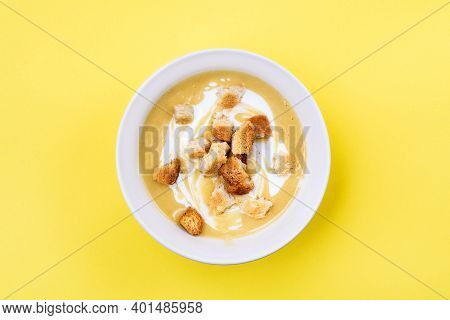 Creamy Chicken And Zucchini Thick Soup Served With Integral Bread Croutons In Whitek Bowl On Yellow