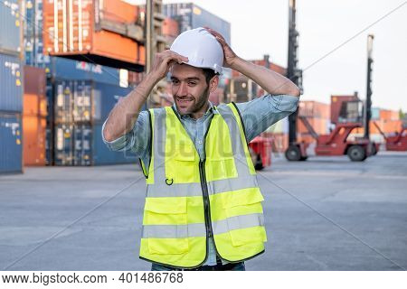 Foreman Engineer Or Cargo Container Worker Hold Hardhat And Stand In Front Of Cranes And Stack Of Sh