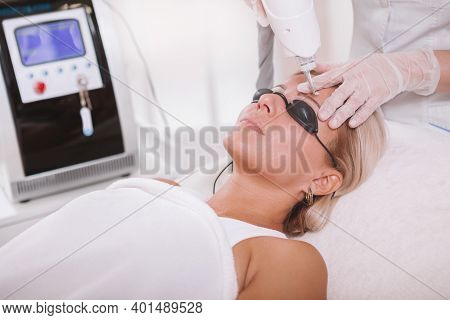 Attractive Woman Getting Eyebrow Tattoo Removed At Beauty Salon. Cosmetologist Removing Tattooed Eye