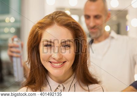 Close Up Of A Lovely Beautiful Woman Smiling Joyfully, Professional Hairdresser Using Hair Spray Fix